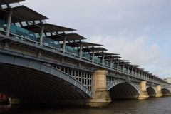 Blackfriars London Train Station Bridge. Lateral view of the bridge over the River Thames that supports the Blackfriars train station that provides transport for Royalty Free Stock Photos