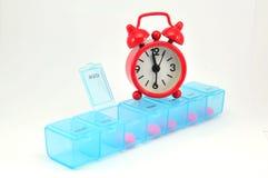 每周药片配件箱和在空白blackground的红色时钟 免版税库存照片