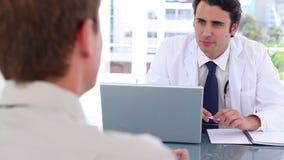 Blackhaired доктор разговаривая с его пациентом сток-видео