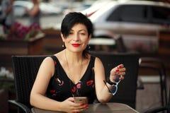 Blackhaired Frau der stilvollen Abkürzung, die an einem Tisch im Caférestaurant wartet stockbilder