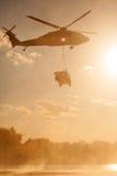 Blackhawk helikopter som bär Humvee Arkivbild