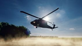 A Blackhawk military helicopter lands on a dusty road on a clear day in a deserted area. Produced in 4K stock video footage