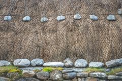 Blackhouse thatched roof detail with thatch, stone and rope royalty free stock photography