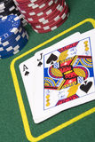 Blackjack. Game of blackjack at a casino with chips on a green blackjack table Royalty Free Stock Image