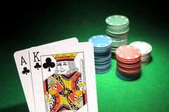 Blackjack. An ace and a king of clubs with stacks of casino chips in the background. Shallow DOF royalty free stock photo