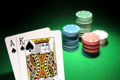 Blackjack. An ace and a king of spades with stacks of casino chips in the background. Shallow DOF Stock Image