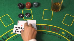 Blackjack Player Split Aces And Win In Casino. Blackjack gambling game. Female player bet chips. Dealer put cards on green deck table. Gambler deal two aces stock footage