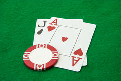 Blackjack hand with casino chip on green  table Royalty Free Stock Images