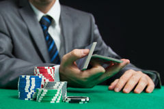 Blackjack Or Poker Game, Casino Worker Shuffling Cards. Blackjack Or Poker Game, Colourful Casino Chips On The Front And  Casino Worker Shuffling Cards On the Royalty Free Stock Photography
