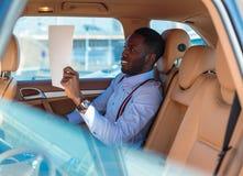 Blackman in een blauw overhemd zit op auto` s achterbank royalty-vrije stock fotografie