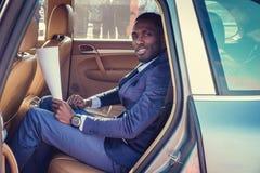 Blackman in een kostuum in de auto stock fotografie