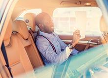 Blackman i en blå skjorta sitter på baksätet för bil` s royaltyfri bild