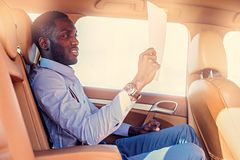 Blackman i en blå skjorta sitter på baksätet för bil` s royaltyfria foton