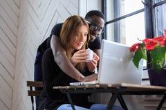 Blackman und junge Frau, die mit Laptop arbeiten Stockbild