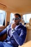 Blackman w kostiumu w samochodzie obrazy stock