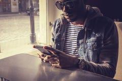 Blackman in zonnebril die smartphone gebruiken stock fotografie
