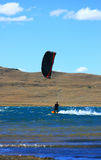 Blackred kitesurfer cruising Stock Images