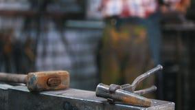 Blacksmith на работе близкая поднимающая вверх съемка инструментов: молоток и vedge видеоматериал