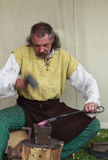 The blacksmith. Dinamic image of a blacksmith doing his job.Medieval market show-Arville 23.05.2010 , France Stock Images
