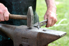 Blacksmith. Oldfashioned blacksmith working on metal horseshoe with hammer Royalty Free Stock Images