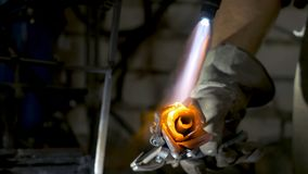 Blacksmith aligns leaves of iron rose and makes the final shape of the flower. Blacksmith makes iron rose Stock Image