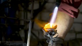 Blacksmith aligns leaves of iron rose and makes the final shape of the flower. Blacksmith makes iron rose Stock Photography