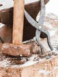 Blacksmith anvil, tongs and hammer in old smithy Royalty Free Stock Photos