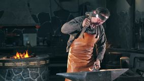 Blacksmith is beating iron with a hammer. Slow motion. Blacksmith is beating iron with a hammer. 4K stock video