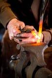 Blacksmith bending a hot metal rod Royalty Free Stock Photos