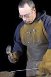 Blacksmith bending a wrought iron rail Stock Image