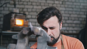 Blacksmith bends metal knife with gripe in workshop forge, portrait Stock Photos