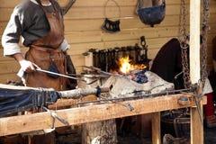 Blacksmith blows the bellows Royalty Free Stock Photo