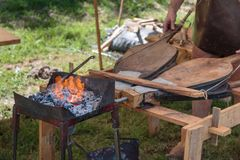 Blacksmith Blows Coals with Bellows. In Outdoor Fair Stock Images