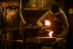 The blacksmith with brush handles the molten metal on the anvil in smithy.  royalty free stock photos