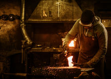 The blacksmith with brush handles the molten metal on the anvil in smithy.  stock photos