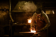 Blacksmith with brush handles the molten metal on the anvil in smithy.  royalty free stock photography