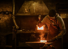 Blacksmith with brush handles the molten metal on the anvil in smithy.  royalty free stock photo