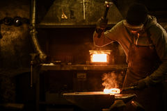 Blacksmith with brush handles the molten metal on the anvil in smithy.  royalty free stock image