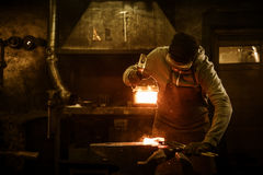 Blacksmith with brush handles the molten metal on the anvil in smithy.  royalty free stock images