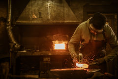Blacksmith with brush handles the molten metal on the anvil in smithy.  stock photography