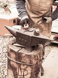 Blacksmith builds an iron sign, in a square in Rovereto for the holiday season royalty free stock photo