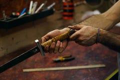 Blacksmith checks sharpening of blade of sword Stock Image