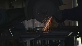Blacksmith cuts iron on machine, slow motion stock video footage