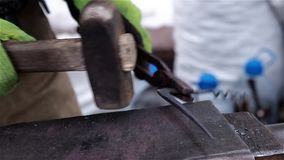 Blacksmith demonstrate their skills and forges corkscrew at Christmas fair stock video footage