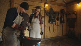 Blacksmith demonstruje proces skucia żelaza pozycja obok uśmiechniętej kobiety zbiory