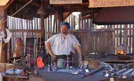 A Blacksmith Dressed in Traditional Outfit. A blacksmith in traditional renaissance 14th to 17th century outfit forging red hot metal into a sword on an anvil Stock Image