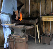 Blacksmith at the Forge. Blacksmith heating iron in a forge stock image