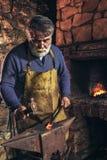 Blacksmith forge iron at work. Senior blacksmith forge iron at work stock images
