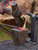 Blacksmith forge a nail with a hammer on the anvil. Russia, Moscow Stock Photos