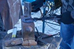 Blacksmith forges horseshoe on anvil. Blacksmith forges a horseshoe on the anvil royalty free stock photo